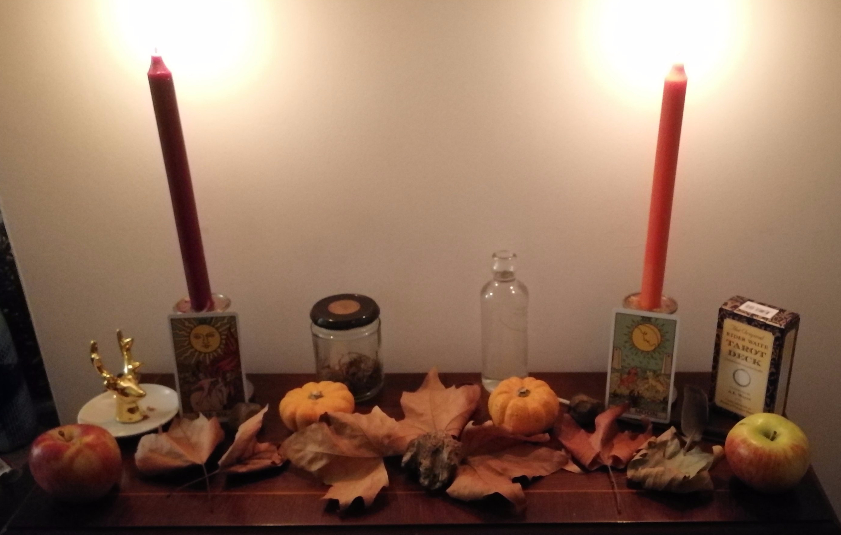 A pagan altar made up of apples, pumpkins, brown leaves and the sun and moon tarot cards